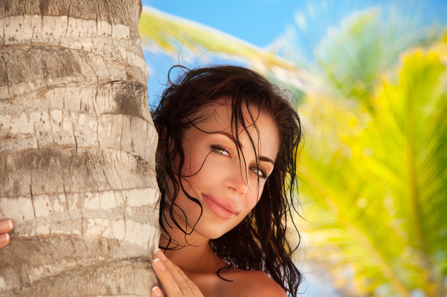 Portrait of a beautiful brunette woman near palm tree, girl spending vacation on a  tropical and exotic resort, happy summer holidays on Caribbean islands